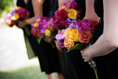 White wedding bouquets mixed jewel tones for maids blue sky maids carry a mix of jewel toned flowers purple vanda orchids yellow orange and magenta roses and purple hydrangea held together with a cuff of green mightylinksfo